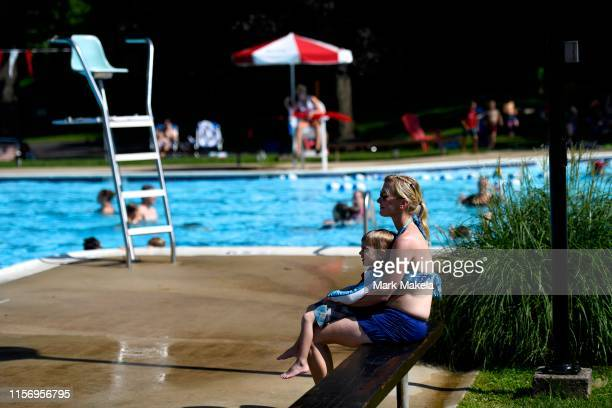 A mother holds her son while watching her other children swim at Karakung Swim Club on July 20 2019 in Ardmore PA With heat indexes reaching 105 to...