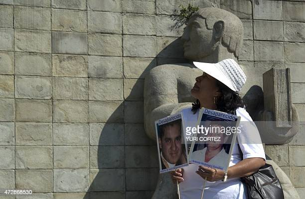 A mother holds pictures of her missing relatives while taking part in a protest during the Mother's Day commemoration in Mexico City on May 10 2015...