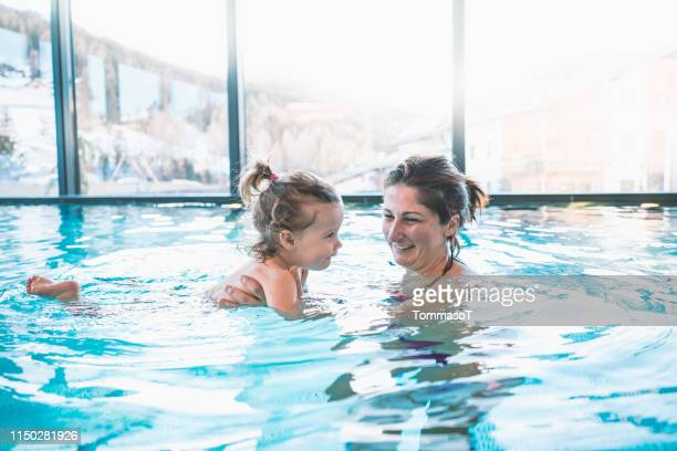 母は泳ぐのを教えるスイミングプールで娘を抱き上げる - 室内プール ストックフォトと画像