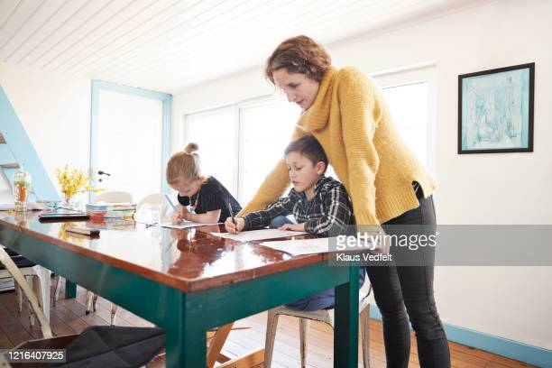 mother homeschooling daughter and son at dining table - education stock pictures, royalty-free photos & images