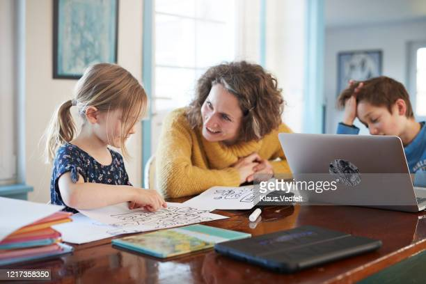 mother homeschooling daughter and son at table - education stock pictures, royalty-free photos & images