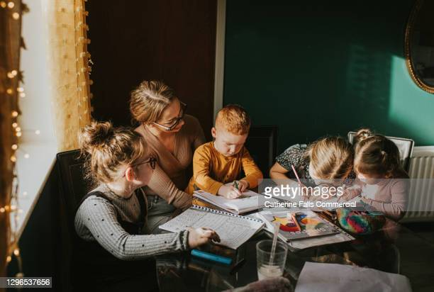 mother homeschooling her 4 children - assistance stock pictures, royalty-free photos & images