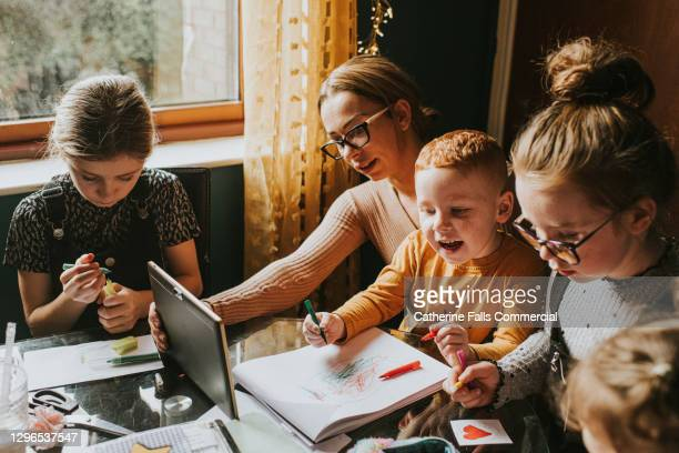 mother homeschooling her children while using a digital tablet - working stock pictures, royalty-free photos & images
