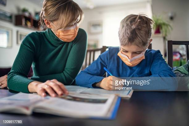 mother homeschooling her son wearing face masks - respirator mask stock pictures, royalty-free photos & images