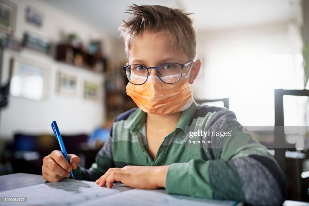 Mother homeschooling her son wearing face masks : Stock Photo
