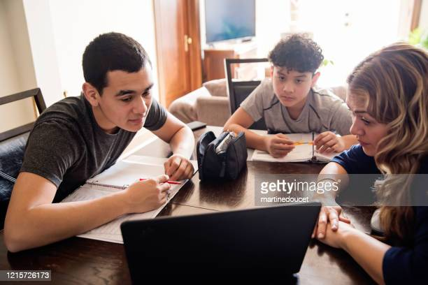 """mother homeschooling teenage boys in self-isolation, covid-19. - """"martine doucet"""" or martinedoucet stock pictures, royalty-free photos & images"""