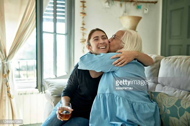 mother hugging and kissing adult daughter - two seater sofa stock pictures, royalty-free photos & images