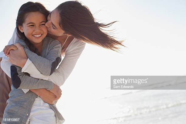 Mother hugging and kissing daughter on beach