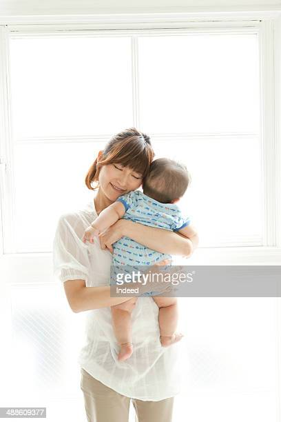 Mother hugging baby boy by window