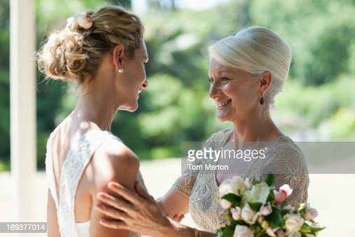 Mother Hugging Bride On Wedding Day Stock Photo