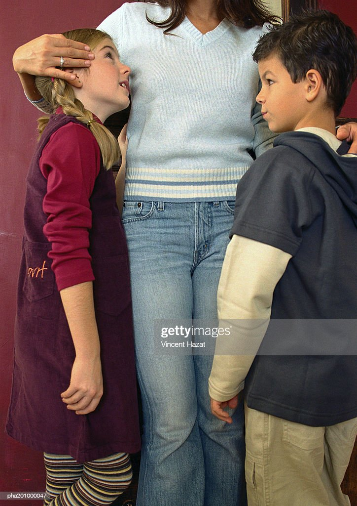 Mother hugging children, standing, full length, close-up. : Stockfoto