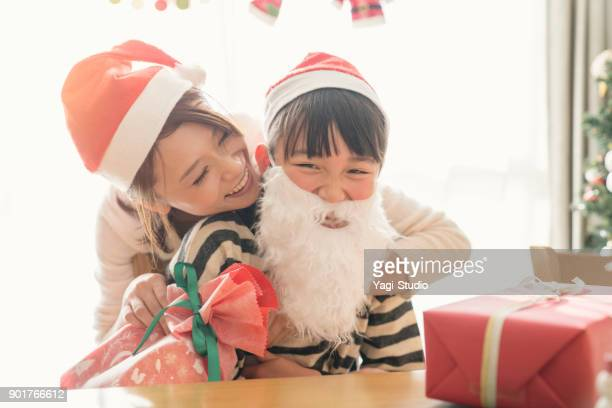 Mother hugging daughter at Christmas party in home