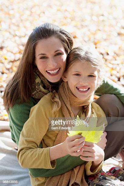 Mutter umarmen und Tochter holding Herbst leaf