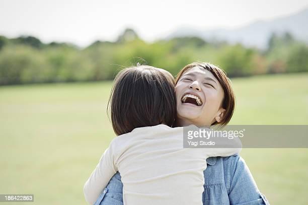 Mother hugging daughter in green