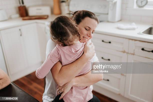 mother hugging daughter in kitchen - zärtlich stock-fotos und bilder