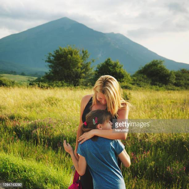 mother hugging daughter in nature - ivanjekic stock pictures, royalty-free photos & images