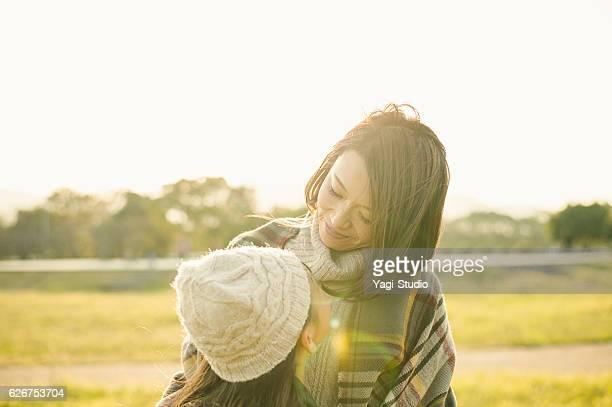 Mother hugging daughter in outdoors