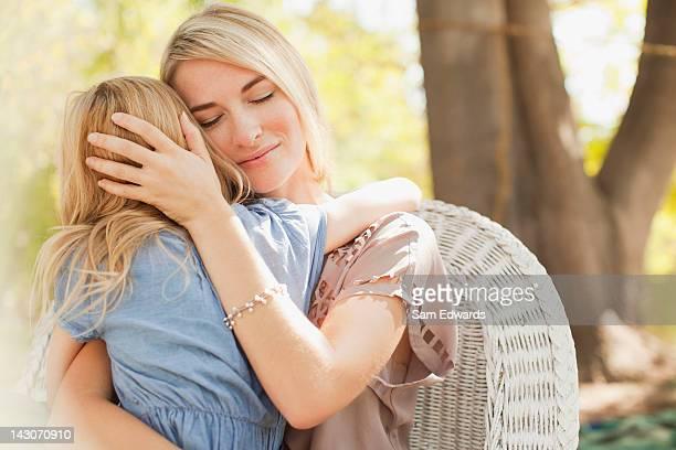 Mère embrassant sa petite fille à l'extérieur