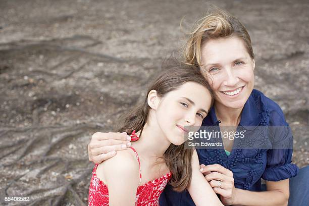 Mother hugging daughter outdoors