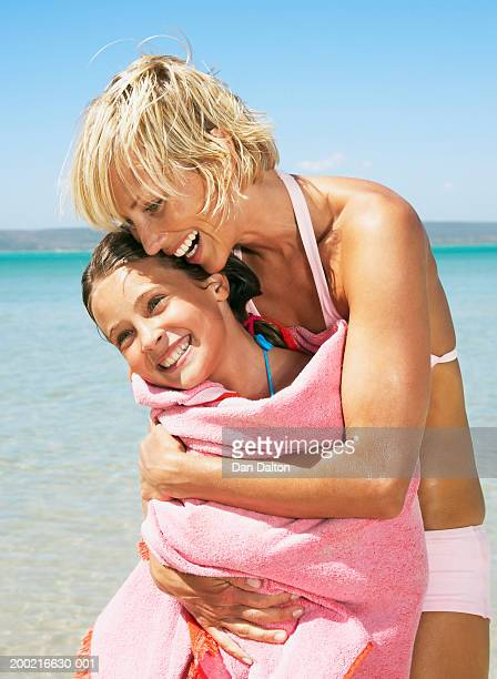 mother hugging daughter (8-10) wrapped in towel on beach, smiling - mother daughter towel stock photos and pictures