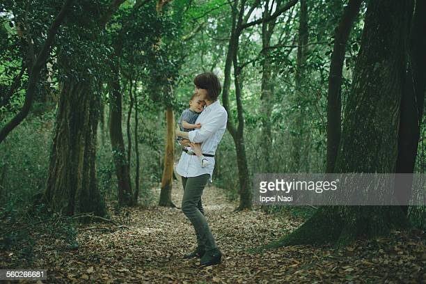 Mother hugging her baby in forest