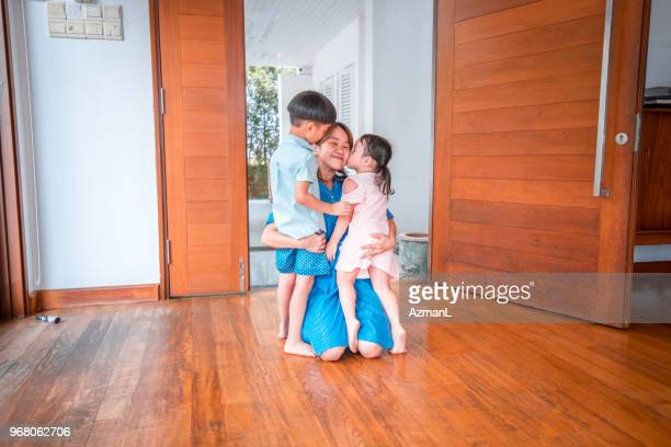 mother hugging her children when coming home - close to stock pictures, royalty-free photos & images
