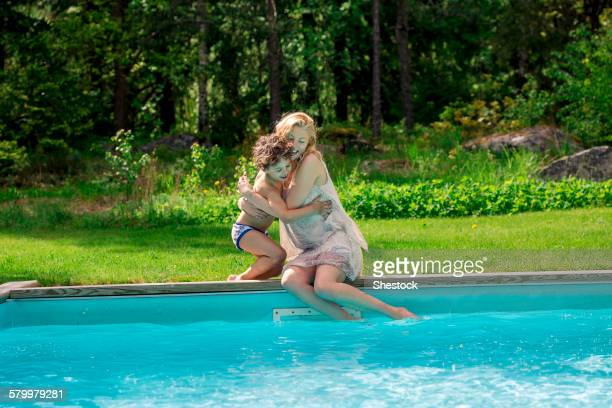Mother hugging son at swimming pool in backyard