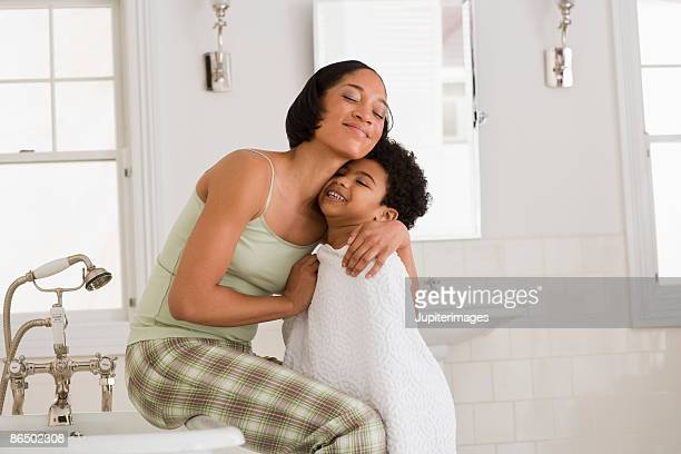 mother hugging son in bathroom - wrapped in a towel stock pictures, royalty-free photos & images