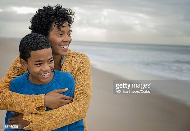 Mother hugging son (10-12) on beach