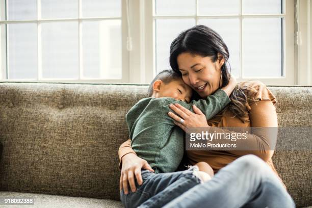 mother hugging son on couch - één ouder stockfoto's en -beelden