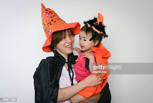 Mother hugging the baby wearing halloween costumes