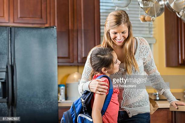 mother hugging young daughter as she leaves for school - little girls giving head stock photos and pictures