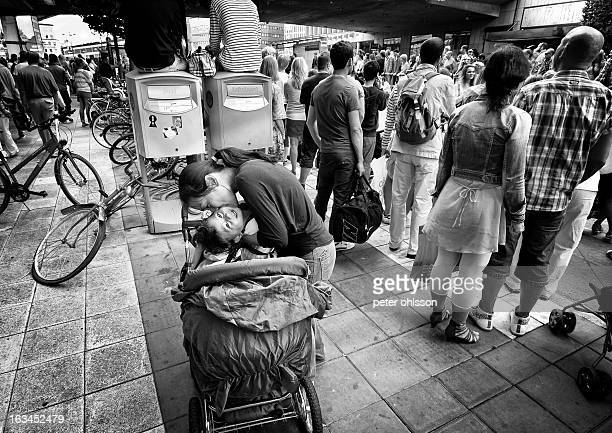 Mother hugs and kisses her baby in the streets of the city