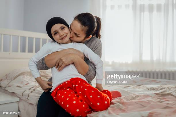 mother hugs and kisses her child with cancer - leukemia stock pictures, royalty-free photos & images