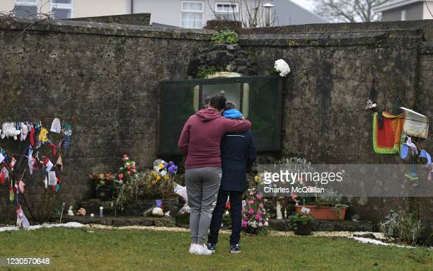 Mother hugs her child after leaving flowers at the shrine which stands on a mass burial site which was formerly part of the Bon Secours Mother and...