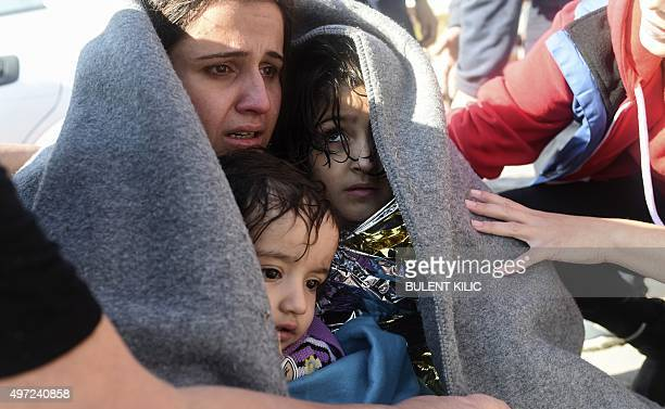 A mother hugs her children after disembarking as migrants and refugees arrive on the Greek island of Lesbos after crossing the Aegean Sea from Turkey...