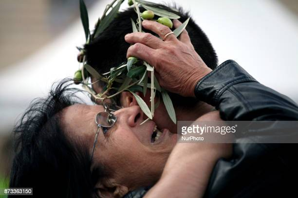 A mother hugs her son at the finish line at the Panathenaic stadium offering him an olive wreath at the 35th Athens Classic Marathon in Athens Greece...