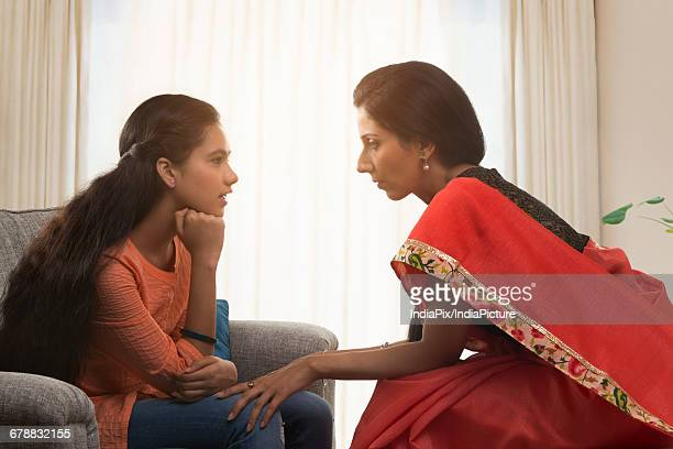Mother in a red sari talking to her teenage daughter in living room