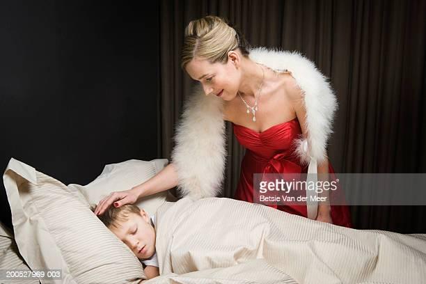 Mother in ballgown stroking head of sleeping boy (8-10) in bed