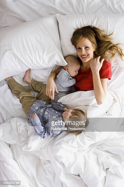 Mutter im Bett mit zwei kleinen Kindern