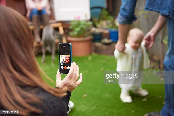 Mother in garden using smartphone to film daughter learning to walk, focus on foreground