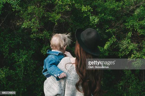 Mother in hat holding child on hands on the background of greenery