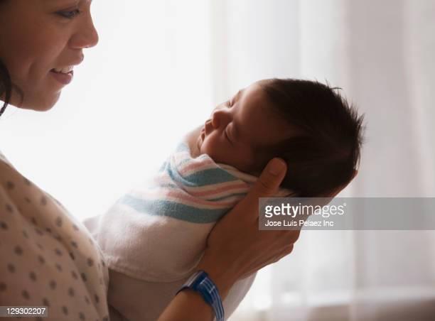 Mother in hospital holding newborn baby girl