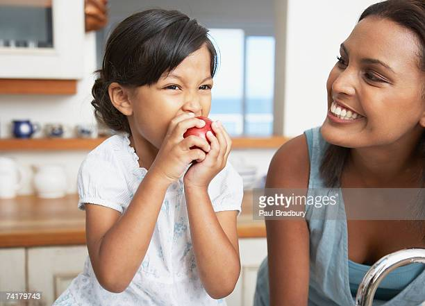 Mother in kitchen with daughter eating red apple