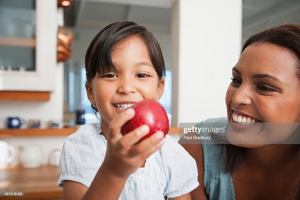 Mother in kitchen with daughter holding red apple : Stock Photo