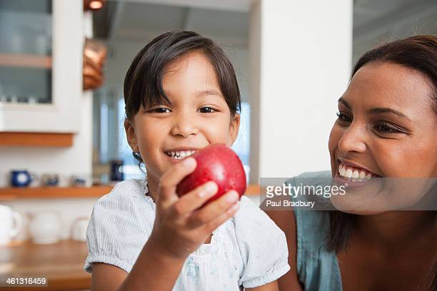 Mother in kitchen with daughter holding red apple