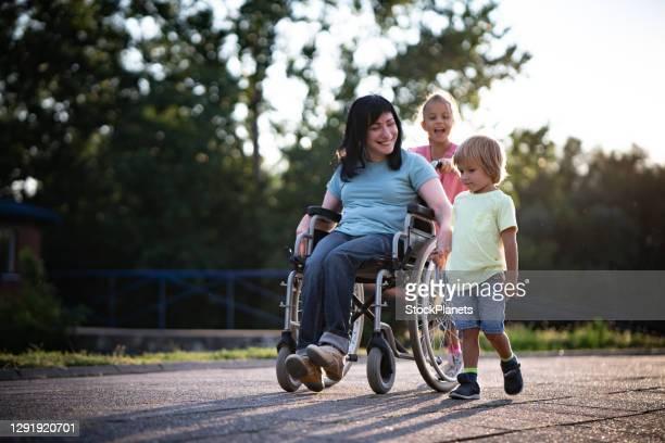 車椅子の母親は子供たちが屋外で時間を過ごす - 麻痺 ストックフォトと画像