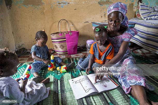 A mother interacting with her daughter and using reading and coloring books as part of TOSTAN's Reinforcement of Parental Practices Module where by...