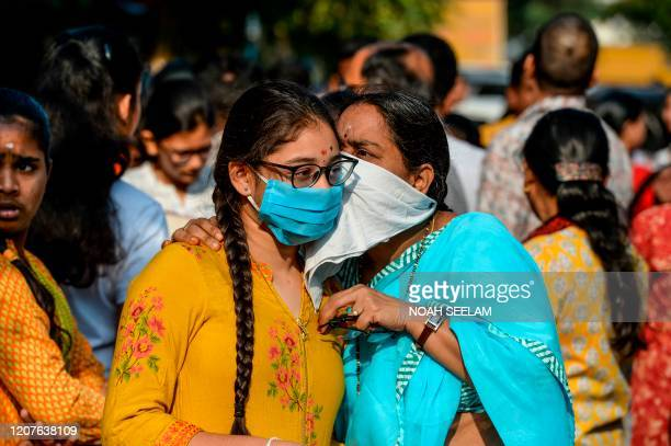 A mother interacts with her daughter wearing a facemask amid concerns over the spread of the COVID19 coronavirus as she attends the first day of her...
