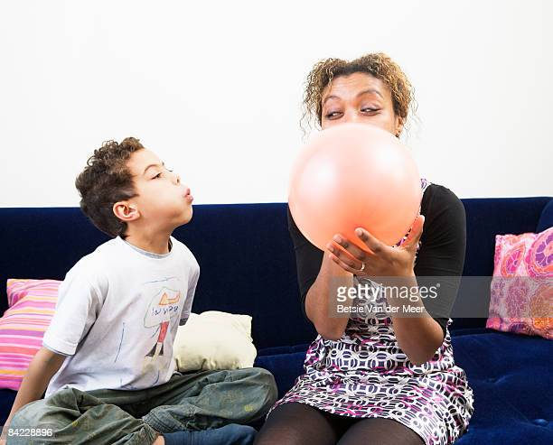 Mother is blowing up balloon with child's help.
